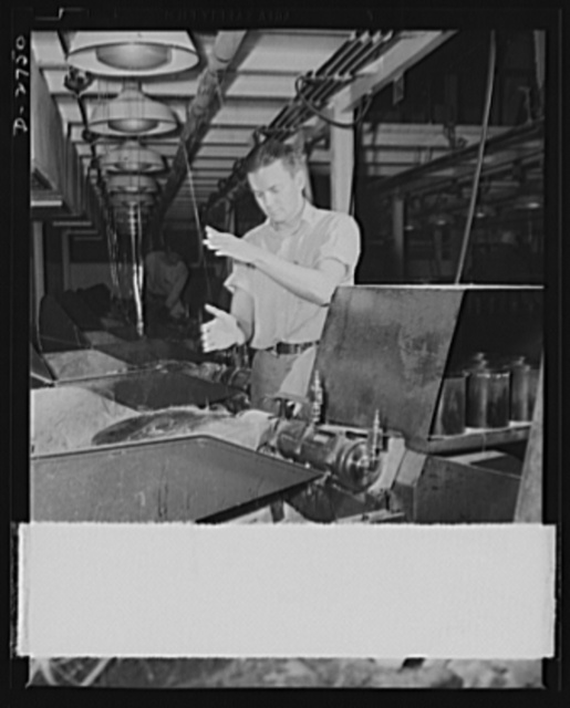 Fiberglass manufacture, Owens-Corning, Toledo, Ohio. A worker in a plant of the Owens-Corning Fiberglass Corporation guides a strand of 204 glass filaments from the forming machine above to the gathering tube on which it is wound at more than a mile a minute