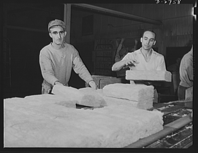 Fiberglass manufacture, Owens-Corning, Toledo, Ohio. A worker in a plant of the Owens-Corning Fiberglass Corporation is packaging bats of lightweight, inorganic, firesafe building insulation. Recent findings by the U.S. Bureau of Mines show that adequate home insulation can save over a billion dollars a year in fuel and release transportation facilities required for the war effort