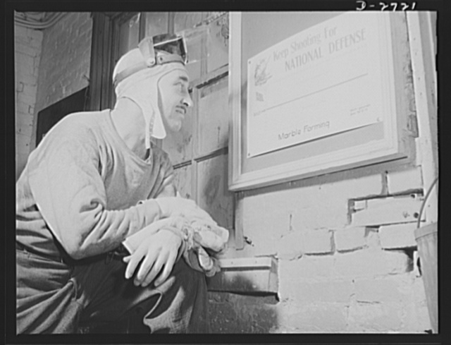 Fiberglass manufacture, Owens-Corning, Toledo, Ohio. A workman in the marble forming department of a plant of the Owens-Corning Fiberglass Corporation looks at the record to see whether his department is meeting war production needs. His smile indicates that he is hitting the bull's-eye for national defense