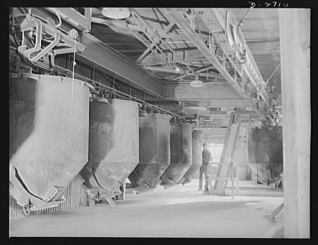 Fiberglass manufacture, Owens-Corning, Toledo, Ohio. Along an overhead monorail system, cans containing the carefully compounded ingredients of the batch move to the huge furnaces for conversion into molten glass from which fiberglass materials are manufactured in a plant of Owens-Corning Fiberglass Corporation