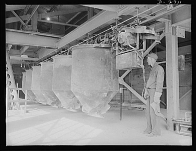 Fiberglass manufacture, Owens-Corning, Toledo, Ohio. Along an overhead monorail system, cans containing the carefully compounded ingredients of the batch, move to the huge furnaces for conversion into molten glass from which fiberglass materials are manufactured in a plant of Owens-Corning Fiberglass Corporation