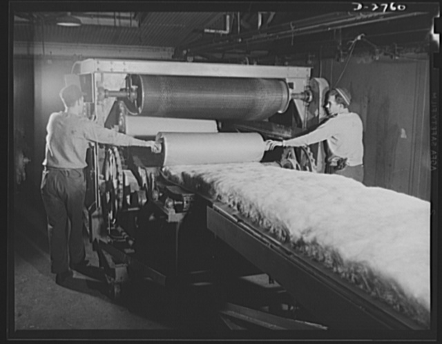 Fiberglass manufacture, Owens-Corning, Toledo, Ohio. As the blanket of fiberglass thermal insulation moves along on a conveyer, it is packaged in rolls. These rolls then are taken elsewhere in the plant to be fabricated into pipe covering or insulating blocks