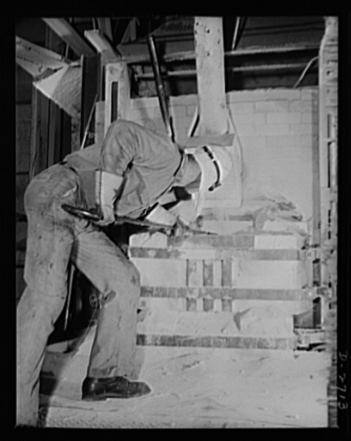 """Fiberglass manufacture, Owens-Corning, Toledo, Ohio. Feeding the batch into what glass men call """"the doghouse""""--the charging end of a furnace--this worker is servicing one of the tanks used to manufacture fiberglass thermal and acoustical insulation in a plant of Owens-Corning Fiberglass Corporation"""