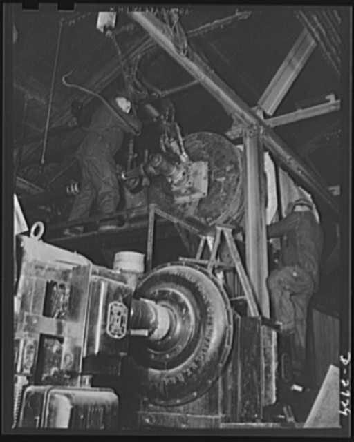Fiberglass manufacture, Owens-Corning, Toledo, Ohio. Fiberglass metal mesh blankets made of glass fiber thermal insulation sandwiched between facings of metal mesh are being installed around a boiler in the powerhouse of a plant of the Owens-Corning Fiberglass Corporation