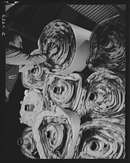 Fiberglass manufacture, Owens-Corning, Toledo, Ohio. Fiberglass thermal insulation is packaged in rolls and taken elsewhere in a plant to be fabricated into pipe covering or insulating blocks