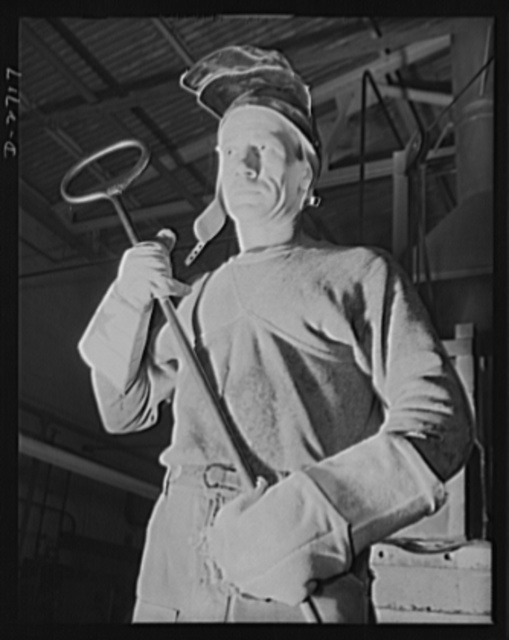 Fiberglass manufacture, Owens-Corning, Toledo, Ohio. In a plant of the Owens-Corning Fiberglass Corporation, a worker stands ready with his iron ladle to transport molten glass from the furnace to the machine that forms it into glass marbles from which it is converted into glass fibers. As one of the men behind the men behind the guns, his work is an essential step in the production of fiberglass yarns being used in a wide variety of military and naval applications
