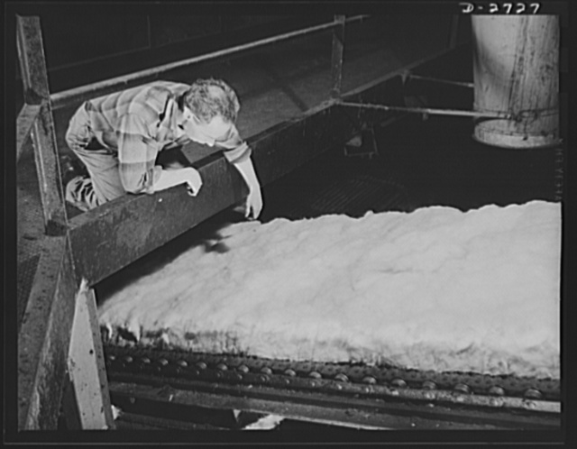 Fiberglass manufacture, Owens-Corning, Toledo, Ohio. In a resilient, lightweight blanket of interlaced fibers, fiberglass thermal insulation is carried along from the furnaces where it is produced to be packaged or further fabricated into the forms required by Army and Navy specifications