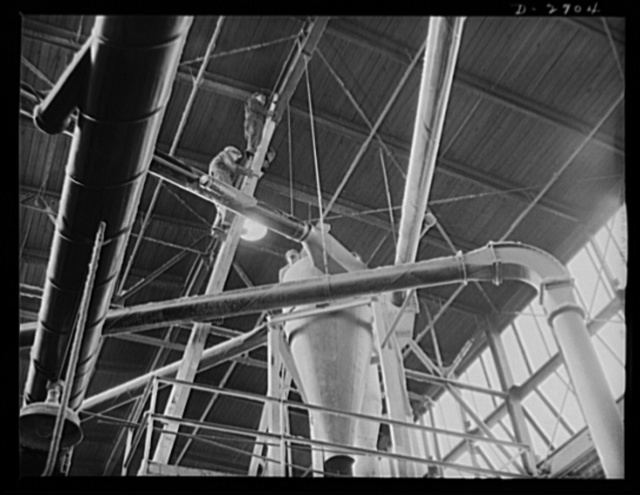 Fiberglass manufacture, Owens-Corning, Toledo, Ohio. In the plant where fiberglass materials are manufactured, as in all other plants where demands for war production are being met, increased maintenance to prevent downtime on vital equipment. Here workmen, high over a glass furnace, are installing equipment to conserve materials