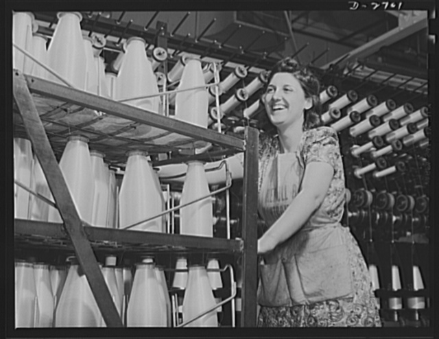 Fiberglass manufacture, Owens-Corning, Toledo, Ohio. Not bottles of milk, but bobbins of glass yarn. From the twisting frames where glass fiber is converted into fiberglass yarns of standard construction, the worker takes the all-glass material to the weaving department for fabrication into tapes and cloths