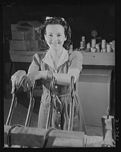 Fiberglass manufacture, Owens-Corning, Toledo, Ohio. Pretty worker in a paint shop of the Owens-Corning Fiberglass Corporation is cutting wafer-thin bonded mats of glass fiber for use as retainer mats in storage batteries supplied under Army and Navy specifications for storage batteries in submarines, tanks, and rough-riding reconnaisance cars