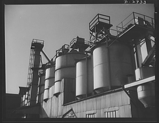Fiberglass manufacture, Owens-Corning, Toledo, Ohio. Section of the batch house at a plant of the Owens-Corning Fiberglass Corporation. In the bins are stored the raw materials for the batch from which fiberglass materials vital to the war effort are produced