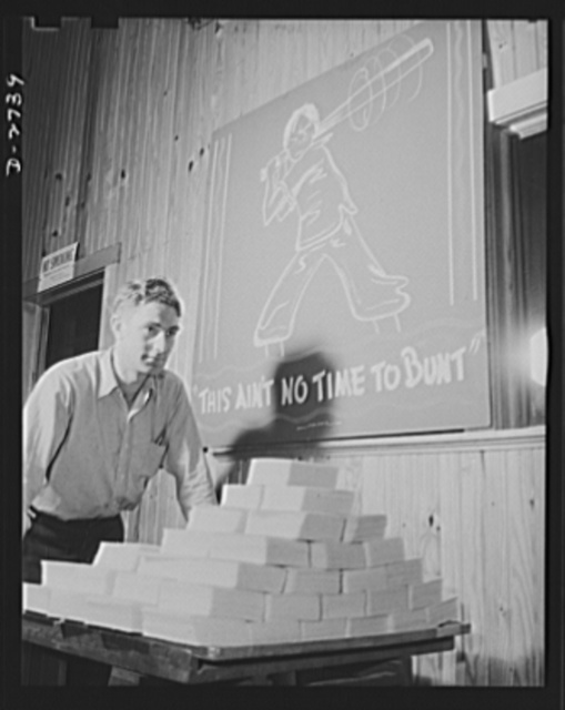 """Fiberglass manufacture, Owens-Corning, Toledo, Ohio. """"This is ain't no time to bunt."""" And this workman at a plant of Owens-Corning Fiberglass Corporation is batting out a hit by speeding carefully inspected packs of fiberglass retainer mats to the shipping department. These are supplied under Army and Navy specifications for storage batteries, to be used in submarines, tanks, and rough-riding reconnaisance cars"""