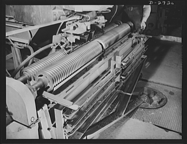 Fiberglass manufacture, Owens-Corning, Toledo, Ohio. This is the machine that forms clear glass marbles in a plant of the Owens-Corning Fiberglass Corporation. Marbles are fed as raw material into electric furnaces from which they are drawn into fibers one-twentieth the size of human hair