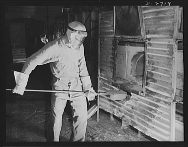 Fiberglass manufacture, Owens-Corning, Toledo, Ohio. This worker is ladling white-hot molten glass from a furnace in a plant of the Owens-Corning Fiberglass Corporation. When viscosity of the molten glass is at the point required by rigid quality control specifications, it will be used to form glass marbles from which glass yarns are drawn in another operation