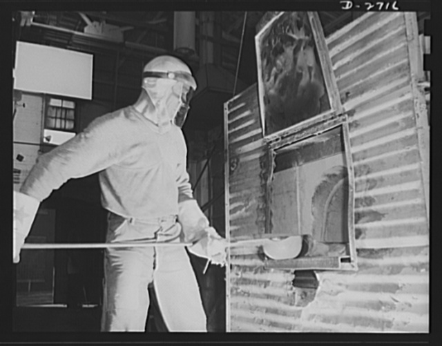 Fiberglass manufacture, Owens-Corning, Toledo, Ohio. This worker is ladling white-hot molten glass from a furnace in a plant of Owens-Corning Fiberglass Corporation. When viscosity of the molten glass is at the point required by rigid quality control specification, it will be used to form the glass marbles from which glass yarns are drawn in another operation