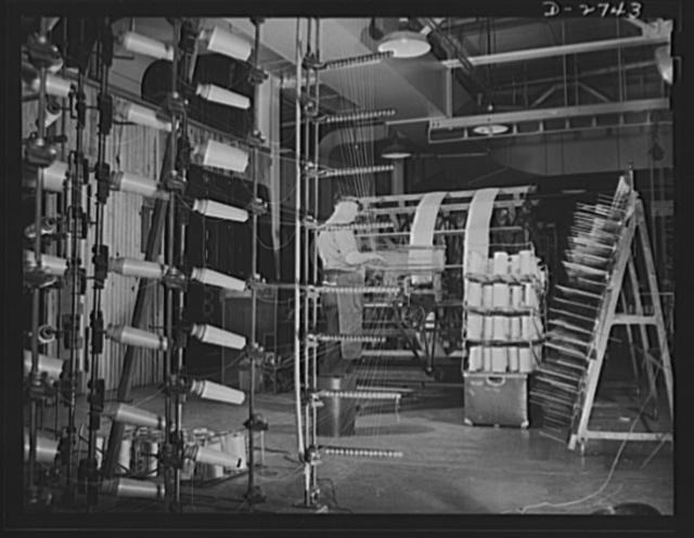 Fiberglass manufacture, Owens-Corning, Toledo, Ohio. Warp yarns of fiberglass are being paralleled on a beam preparatory to weaving all-glass fabrics