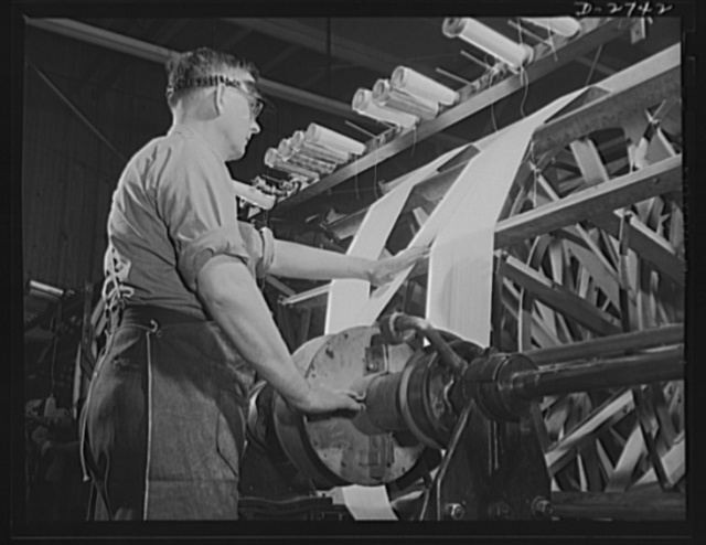 Fiberglass manufacture, Owens-Corning, Toledo, Ohio. Warp yarns of fiberglass are being paralleled on a beam preparatory to weaving all-glass fabrics