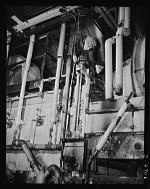 Fiberglass manufacture, Owens-Corning, Toledo, Ohio. Workmen in a plant of the Owens-Corning Fiberglass Corporation are installing the gas-firing lines on a newly-built furnace to expand manufacturing capacity for thermal and acoustical insulation needed in the battle for production