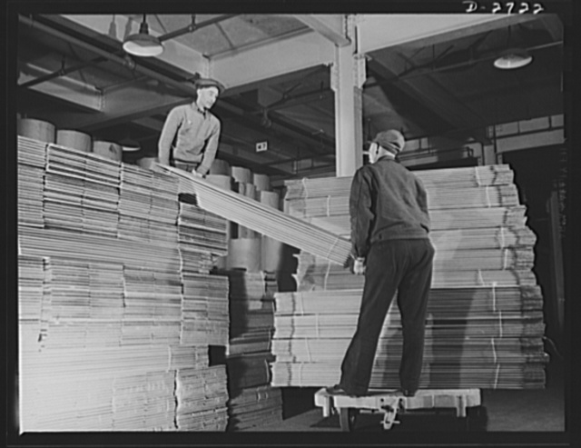 Fiberglass manufacture, Owens-Corning, Toledo, Ohio. Workmen in a plant of the Owens-Corning Fiberglass Corporation move cartons to the production line for packaging fiberglass thermal and acoustical insulation