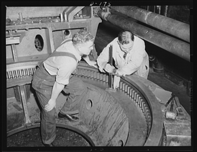Firm understanding. The big base ring for an 8-inch gun, railway carriage, is inspected in an eastern arsenal