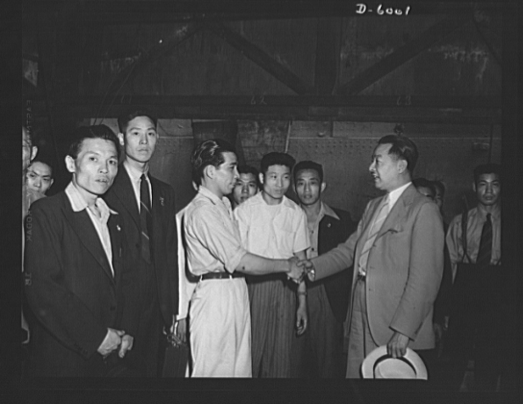 First Chinese seamen granted shore leave in wartime America. Chinese seamen on United Nations' vessels may now obtain shore leave in American ports. Heretofore, because of the large number of desertions by Chinese crew members, alien seamen of Chinese nationality have been detained on board when their ships touched American ports. As a result of conferences between representatives of the Chinese Embassy, the Recruitment and Manning Organization of War Shipping Administration, and the Immigration and Naturalization Service of the Department of Justice, Chinese seamen may now be granted shore leave if guarantees are given that they will not desert. Chinese Counsul General Lee (holding hat) greeting  one of his countrymen from the crew of a British vessel in New York. Lee met the men on arrival and explained the rules under which, for the first time in warring America, they were permitted ashore during their ship's stay in port