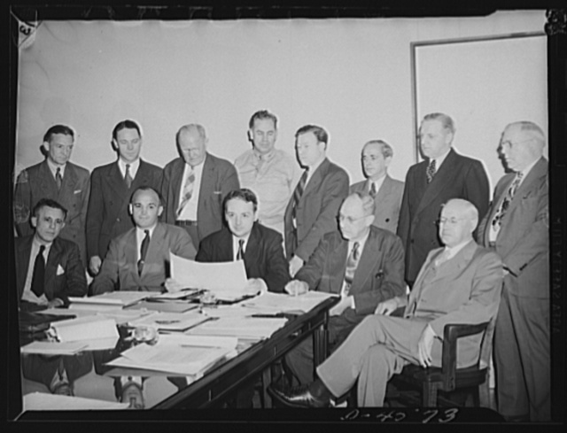 First meeting of labor management policy committee of the War Manpower Commission. Seated -- left to right: Fowler Harper, deputy chairman of War Manpower Commission (WMC); R. Conrad Cooper of Wheeling Steel Corporation; Arthur S. Flemming of Civil Service Commission, chairman; Clinton S. Golden, United Steel Workers of America, Congress of Industrial Organizations (CIO); John P. Frey, American Federation of Labor (AFL), president, Metal Trades. Standing -- left to right: R.E. Gillmore, president, Sperry Gyroscope Company; R. Randall Irwin, director, industrial relations, Lockheed Vega Aircraft Corporation; H.A. Enochs, chief of personnel, Pennsylvania Railroad Company; Brigadier General Frank J. McSherry, director of operations, War Manpower Commission; Walter P. Reuther, member of United Automobile Workers, CIO; John Green, Marine and Shiipbuilding Workers, CIO; George Masterton, Steam Fitters and Plumbers, AFL; Joseph S. McDonagh, secretary treasurer, Building Trades, AFL