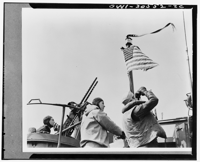 Flags flies over PT boat. In sea warfare since Pearl Harbor, the Navy tinset PT boats have frequently proved to be a deadly match for warships, submarines and merchant men. Their hulls are thin and their sides are small but their offensive and defensive armament is varied and effective. It consists of fifty caliber anti-aircraft machine guns, torpedoes and depth charges. These training pictures were taken at the United States Navy Motor torpedoed boat training center, Melville, Rhode Island. In their training, the tiny PT boat is learning to be constantly on the alert. In the background a crew member sighted the 50-caliber anti-aircraft machine gun while the officer in the foreground scans the sky for planes