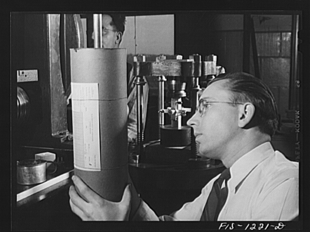 Forest Products Laboratory, Madison, Wisconsin. Testing a block of wood to show the effect of compression parallel to the grain. As pressure is applied to the block, a lamb's roller extensometer is used to plot the effect on a graph
