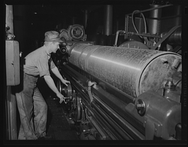 Forged steel to make the lungs of a torpedo. Smoothing down the outside of torpedo air flasks is this man's job. Production is going at top speed at the eastern Navy arsenal in which this equipment is produced