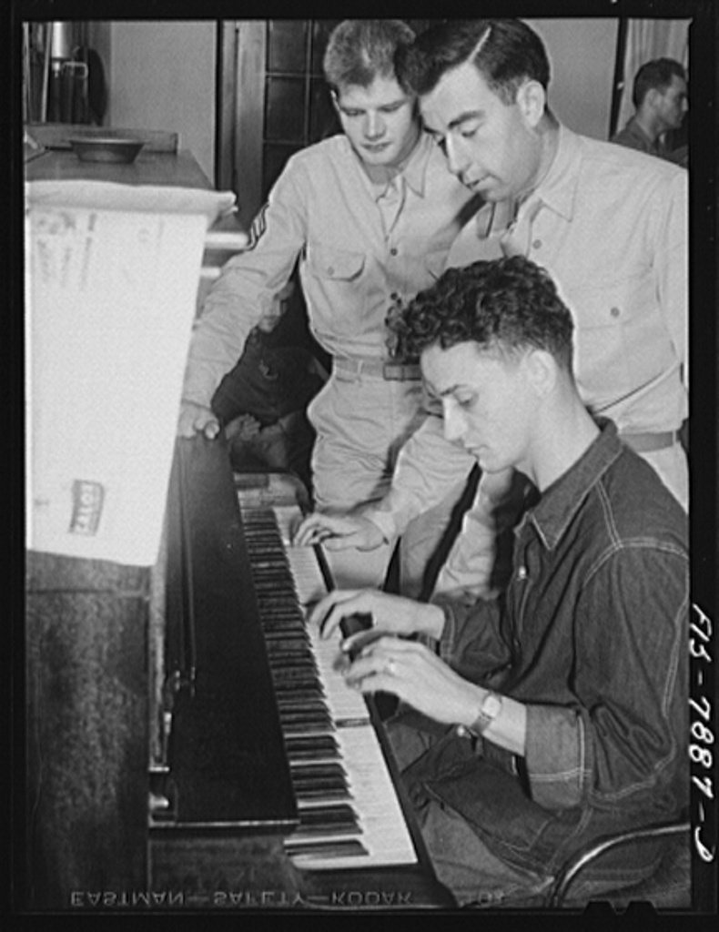 Fort Belvoir, Virginia. A corporal picking out a tune on the piano while Sergeant George Camblair and a friend look on