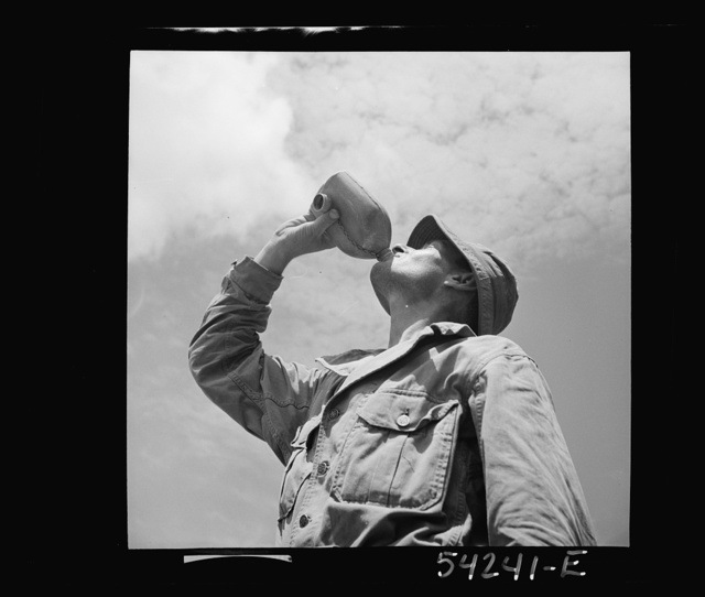 Fort Belvoir, Virginia. A soldier drinking from a G.I. water canteen