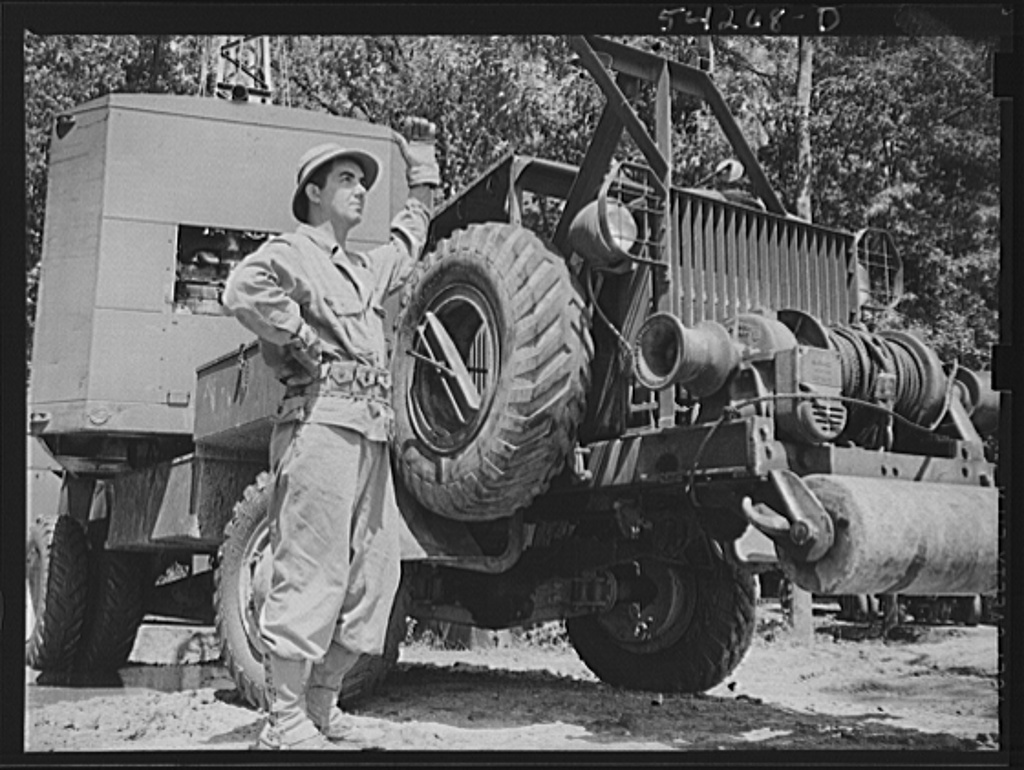 Fort Belvoir, Virginia. A soldier standing beside a truck with a mounted crane on it