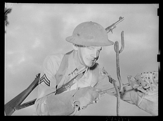 Fort Belvoir, Virginia. A soldier using a barbed wire anchor spike to screw in a picket. He is wearing special gloves that are made for handling barbed wire