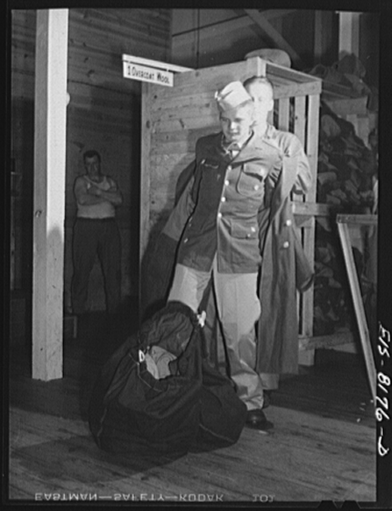 Fort Belvoir, Virginia. Issuing an overcoat to George Camblair at the clothing warehouse