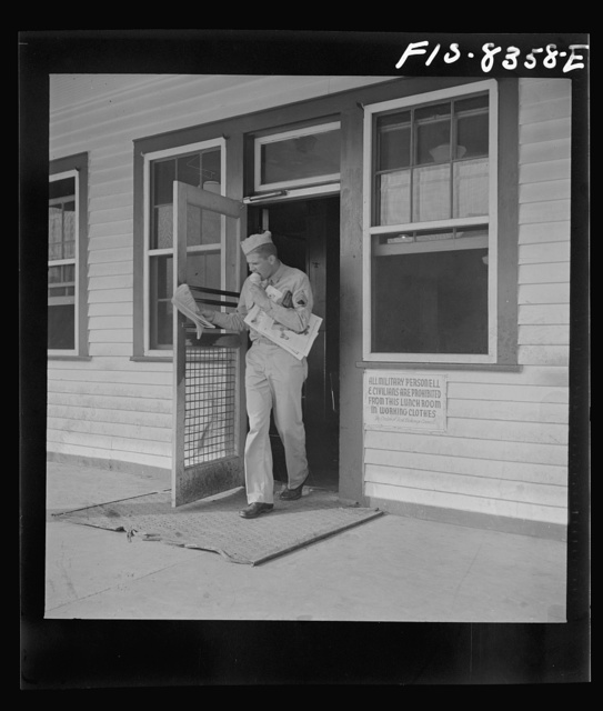 Fort Belvoir, Virginia. Sergeant George Camblair coming out of the post exchange with newspapers and ice cream
