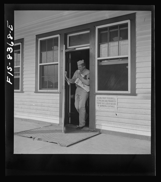 Fort Belvoir, Virginia. Sergeant George Camblair getting some magazines and an ice-cream cone at the post exchange