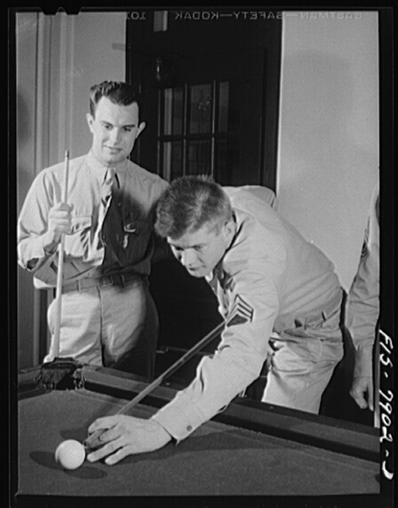 Fort Belvoir, Virginia. Sergeant George Camblair playing a game of billiards with friends in the recreation room at camp while waiting for mess call