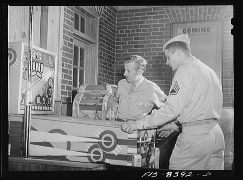 """Fort Belvoir, Virginia. Sergeant George Camblair playing a """"pinball"""" machine at the post exchange"""