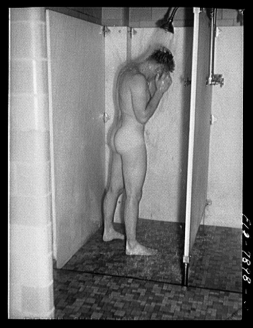 Fort Belvoir, Virginia. Sergeant George Camblair taking a shower at camp