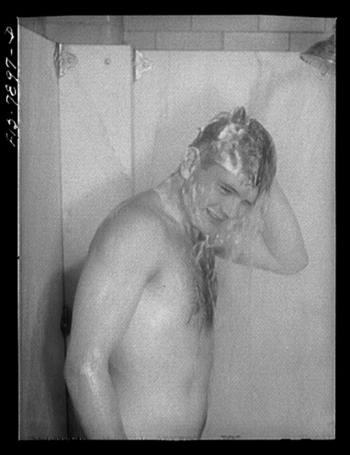 Fort Belvoir, Virginia. Sergeant George Camblair taking a shower before dinner at camp