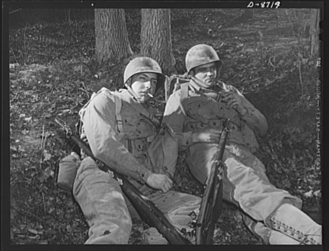 "Fort Belvoir, Virginia. Training sidelights. ""Grabbing a couple of quick smokes"" during a well-earned rest period in training exercises at Fort Belvoir, Virginia. Privates Fred Heindereich and Harry Fleming enjoy cigarettes while waiting for the next orders"
