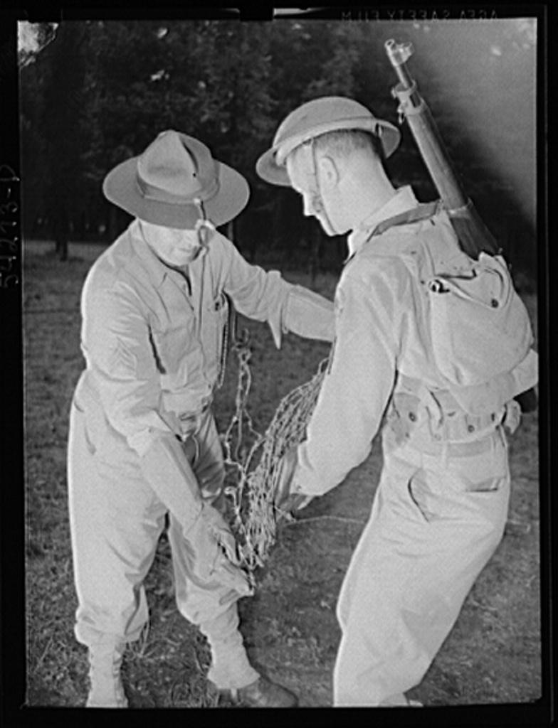 Fort Belvoir, Virginia. Two soldiers, wearing heavy gloves, handling barbed wire steel screw type picket
