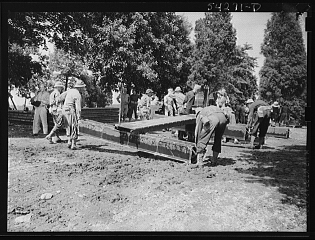 Fort Belvoir, Virginia. United States Army Engineer Corps soldiers in training carrying some heavy equipment for the construction of a bridge or pier