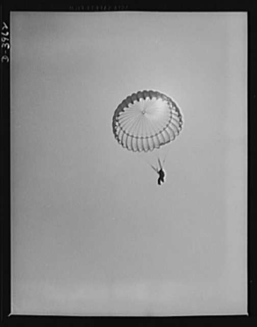 Fort Benning. Parachute troops. Here he comes. A student paratrooper at Fort Benning, Georgia has bailed out of a plane at just the point he figures will let him land at his objective. Just wait a while. He'll be seeing you