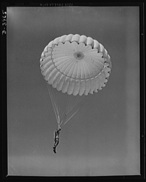 Fort Benning. Parachute troops. Look at that boy come riding a chute like an oldtimer. A student paratrooper at Fort Benning, Georgia has wind currents to think about, and he has his mind on the spot where he wants to land. He's learning to make the kind of landfall he wants