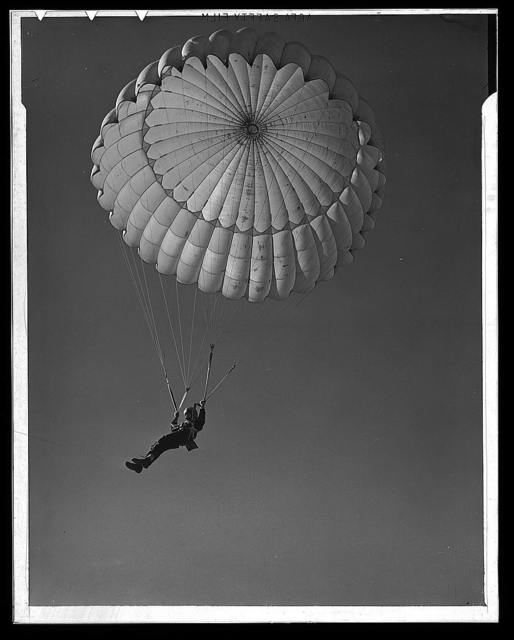 Fort Benning. Parachute troops. Look at that boy come, riding a chute like an oldtimer. A student paratrooper at Fort Benning, Georgia has wind currents to think about, and he has his mind on the spot where he wants to land. He's learning to make the kind of a landfall he wants