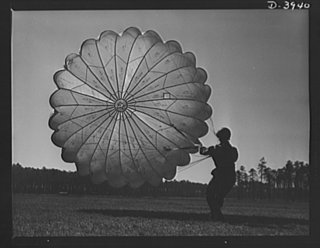 Fort Benning. Parachute troops. Picture of a man doing a good job. He's one of Uncle Sam's student paratroopers at Fort Benning, Georgia, but the way he's getting his chute under control would do credit to an old-timer. A few minutes ago this man bailed out of a high-speed plane at a point calculated to bring him to the spot where he is landing. Good work, soldier