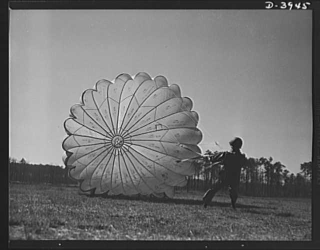 Fort Benning. Parachute troops. Picture of a man doing a good job. He's one of Uncle Sam's student paratroopers at Fort Benning, Georgia, but the way he's getting his chute under contol would do credit to an old timer. A few minutes ago this man bailed out of a high-speed plane at a point calculated to bring him to the spot where he is landing. Good work, soldier