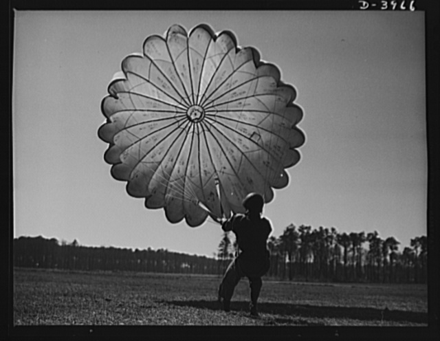 Fort Benning. Parachute troops. Picture of a man doing a good job. He's one of Uncle Sam's student paratroopers at Fort Benning, Georgia, but the way he's getting his chute under control would be credit to an oldtimer. A few minutes ago this man bailed out of a high-speed plane at a point calculated to bring him to the spot where he is landing. Good work, soldier