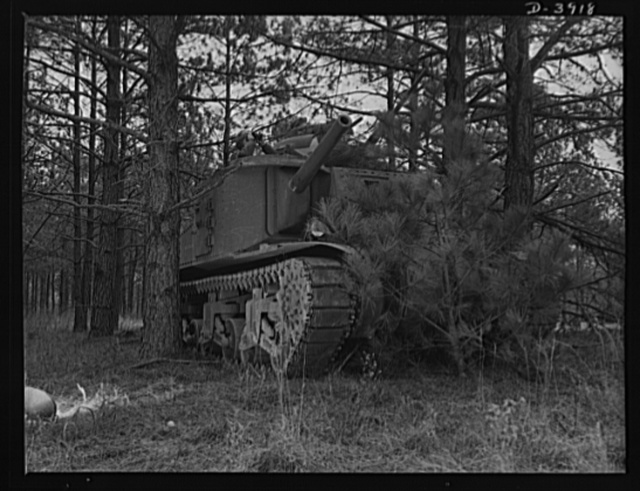 Fort Benning. Tank forces. A medium tank (M-3) partially screened by foliage near Fort Benning, Georgia. Trainees of the armored forces make observations from the turrets as part of the course from which they will graduate as smart and hardened soldiers